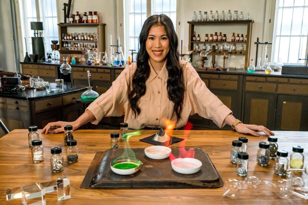 """""""Terra X: - Wunderwelt Chemie - Die Bausteine der Natur"""": Mai Thi Nguyen-Kim lehnt in einem alten Labor an einem Tisch. Vor ihr verschiedene Schalen mit chemischen Stoffen, die in grün, rot und gelb leuchten."""