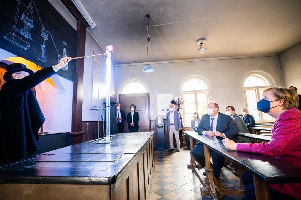 Angela Merkel im Historischen Hörsaal beim Experiment mit Dr. Herbert Lepper (Foto: Bundesregierung/Steffen Kugler)